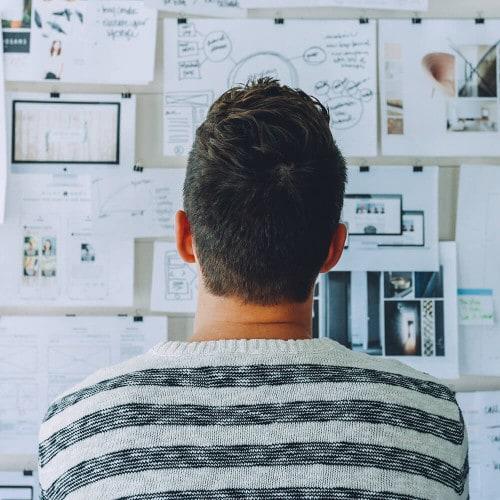 Mann vor einer Pinnwand mit Projektideen